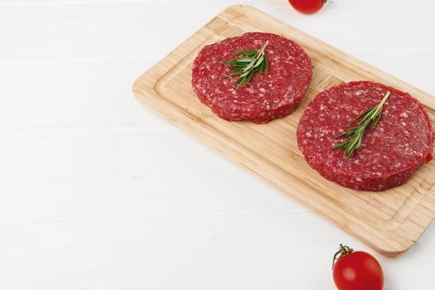Zwei rohe rindfleisch-burger-pastetchen auf holzbrett