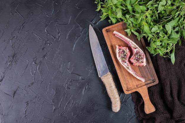 Zwei rohe rindfleischkoteletts auf holzbrett mit frischer minze und messer.