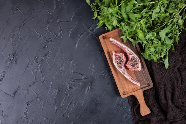 Zwei rohe rindfleischkoteletts auf holzbrett mit frischer minze.