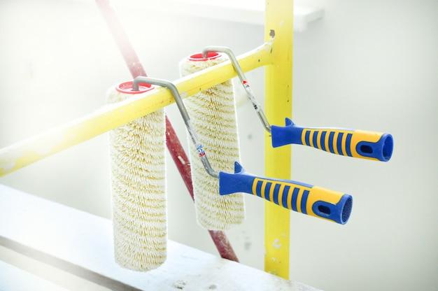 Zwei rollen für das malen von wänden gegen hintergrund der wohnung