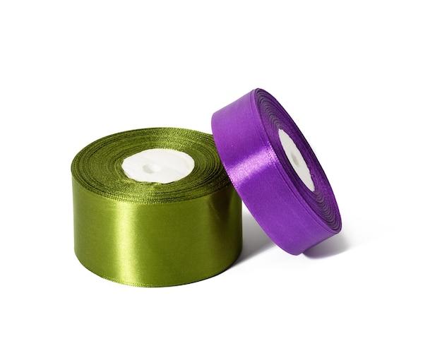 Zwei rollen seidenband grün und lila, wickeldekor, weißer, isolierter hintergrund, nahaufnahme