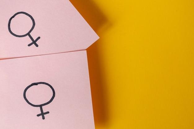 Zwei rosa aufkleber mit den geschlechtssymbolen venus über gelbem hintergrund