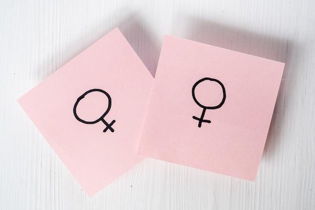 Zwei rosa aufkleber mit geschlechtssymbolen venus auf weißem hintergrund