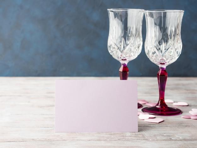 Zwei rosa champagnergläser mit karte des leeren papiers