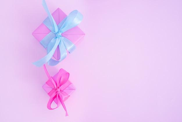 Zwei rosa geschenkboxen mit satinrippen auf rosa hintergrund