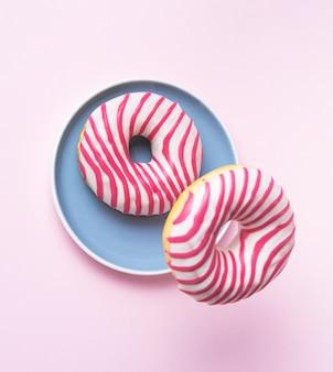 Zwei rosa glasierte donuts fliegen in blauem teller in rosa hintergrund