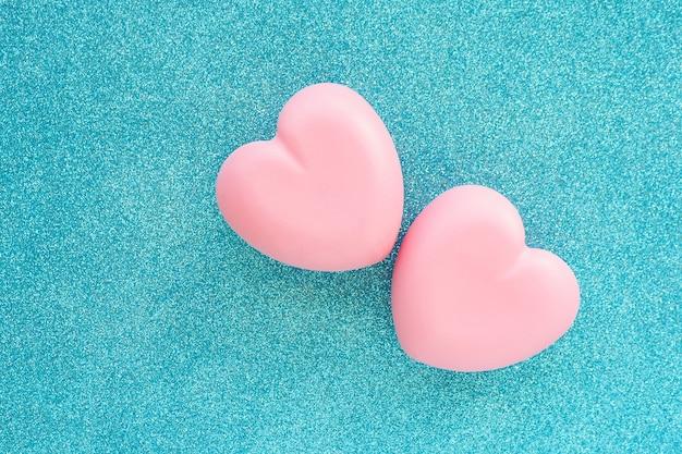 Zwei rosa glitzernde herzen auf einem blau glitzernden hintergrund