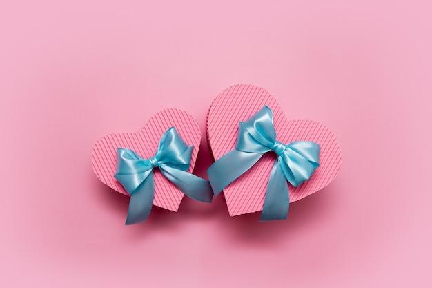 Zwei rosa herzförmige kisten mit einer blauen schleife auf rosa hintergrundgeschenken für valentinstag, geburtstag, muttertag