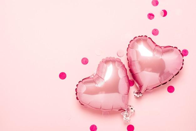 Zwei rosa luftballons in form eines herzens auf einem rosa hintergrund. valentinstag, hochzeitsdekoration. folienkugeln. flachgelegt, draufsicht