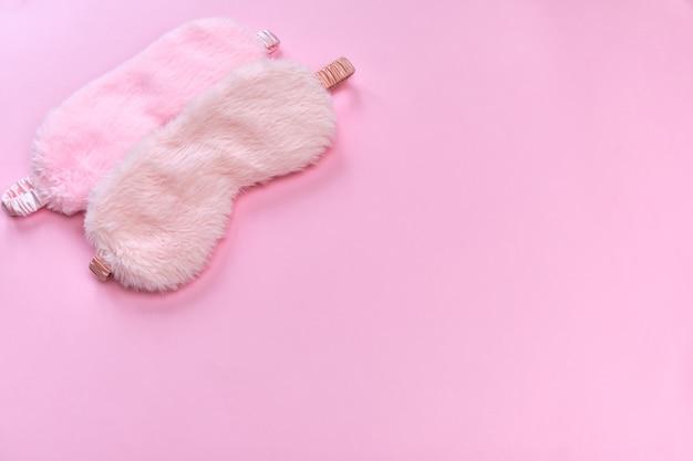 Zwei rosa schlafmasken auf der rosa oberfläche