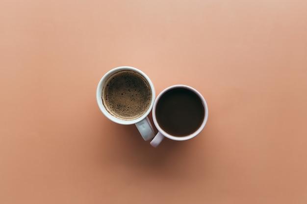 Zwei rosa und blaue kaffeetassen auf beigem hintergrund. hochwertiges foto