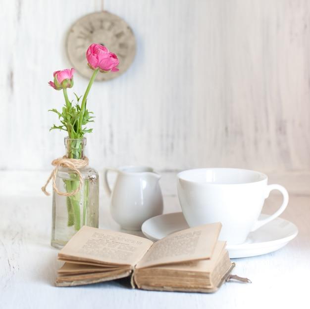 Zwei rosafarbene ranunkeln und ein altes eröffnungsbuch