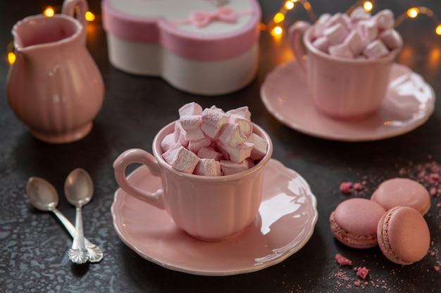 Zwei rosafarbene tassen mit rosa herzförmigen marshmallows