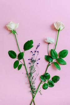 Zwei rosen mit lavendelblumen auf rosa hintergrund