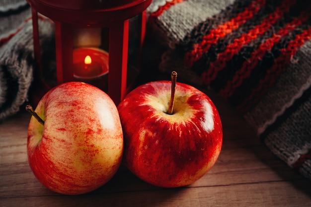 Zwei rote äpfel, wollpullover und eine laterne mit kerze.