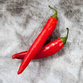 Zwei rote chilis auf grauem hintergrund, ansicht von oben