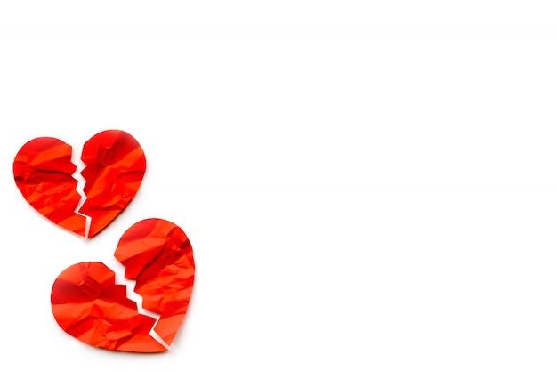 Zwei rote defekte papierherzen auf weißem hintergrund. liebes-konzept. scheidung