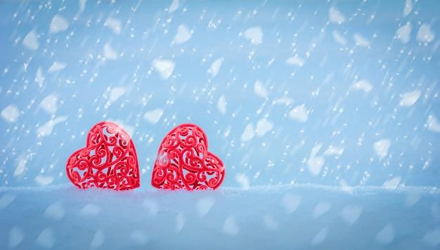 Zwei rote durchbrochene herzen in einer schneeverwehung