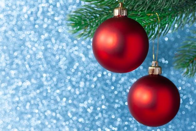 Zwei rote glänzende kugel auf einem neujahrsbaumzweig auf einem blauen unscharfen hintergrund.