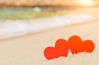 Zwei rote Herzen am Sommerstrand. Liebe, Hochzeit und Valentinstag Konzept.