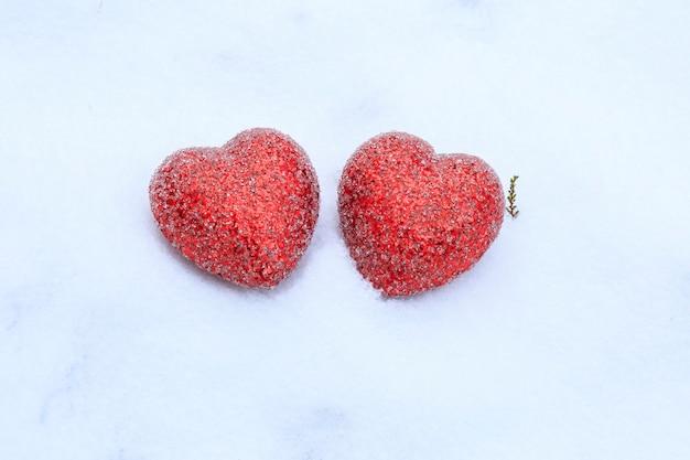 Zwei rote herzen auf dem weißen schnee. feier, valentinsgruß, hochzeitshintergrund.