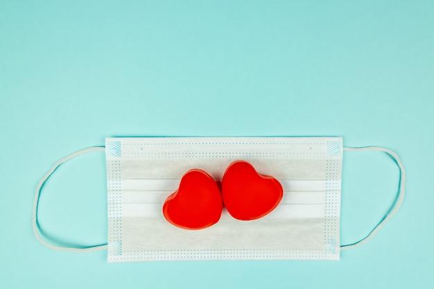 Zwei rote herzen auf der medizinischen schutzmaske, draufsicht. konzept der gesundheitsversorgung, selbstverteidigung. kreative wohnung lag mit kopierraum