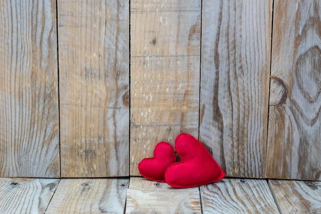 Zwei rote herzen auf einem hölzernen hintergrund für valentinstag