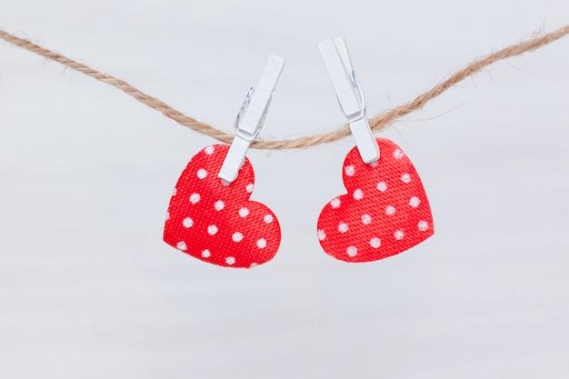 Zwei rote herzen, die an einem thread auf weißem hölzernem hintergrund hängen. valentinstag, liebe, hochzeitskonzept. flachgelegt, draufsicht.