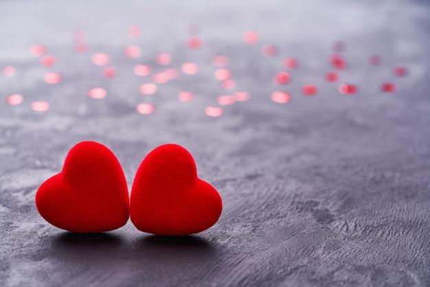 Zwei rote herzen für valentinstaghintergrund.