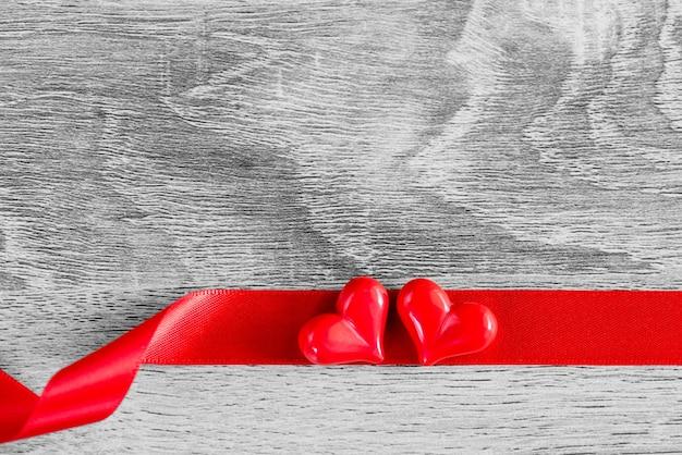 Zwei rote herzen mit rotem band auf hölzernem hintergrund. fröhlichen valentinstag