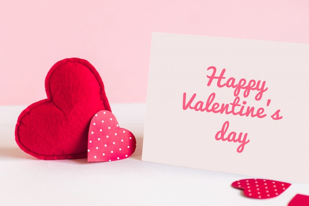 Zwei rote herzen und ein weißes blatt papier mit aufschrift glücklichem valentinstag