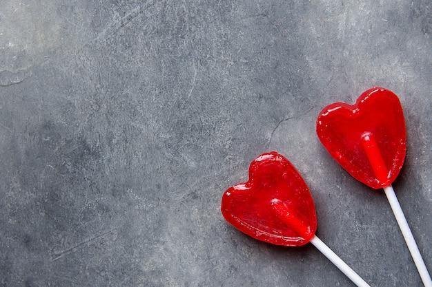 Zwei rote herzform-süßigkeits-lutscher auf stöcken