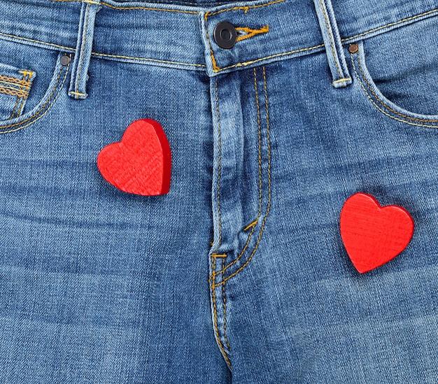 Zwei rote hölzerne herzen auf blue jeans