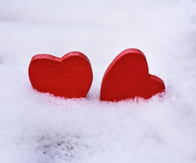 Zwei rote hölzerne herzen liegen auf weißem schnee