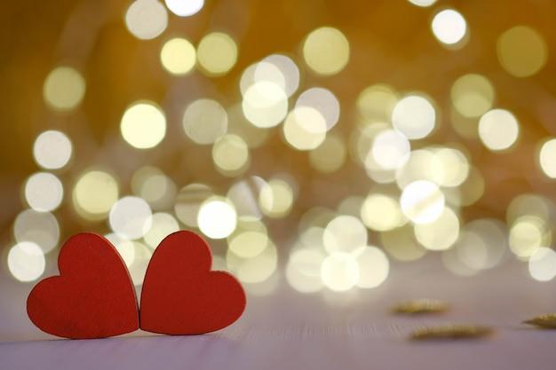 Zwei rote holzherzen auf goldenem bokehhintergrund
