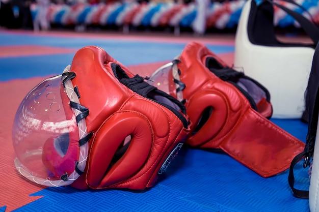 Zwei rote karate-kampfhelme mit durchsichtigen plastikmasken und zwei körperschutzwesten auf dem boden