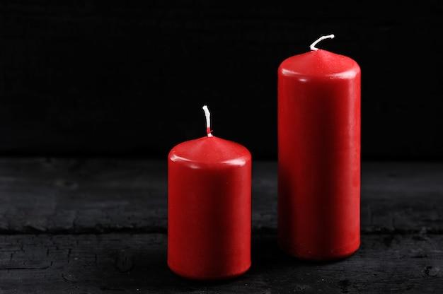Zwei rote kerzen auf einem schwarzen hintergrund