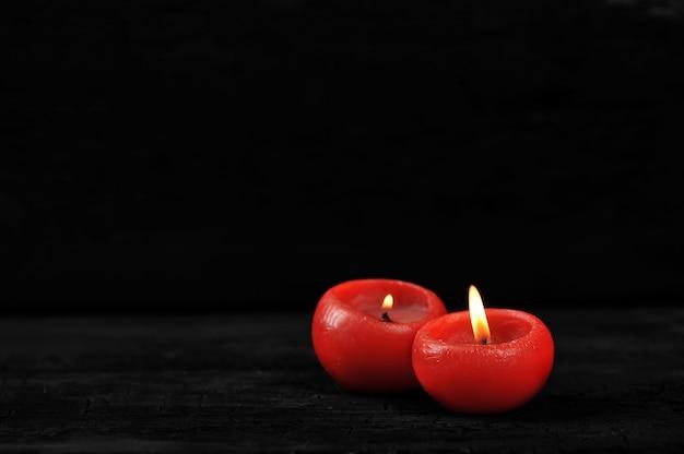 Zwei rote kerzen mit beleuchtetem feuer auf schwarzem hintergrund
