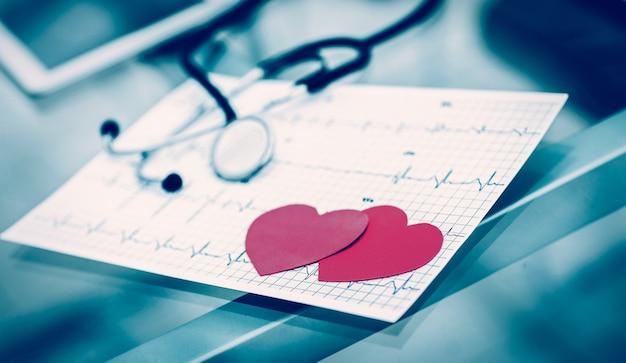 Zwei rote papierherzen auf dem elektrokardiogramm, der kardiologe. das foto ist eine leerstelle für ihren text