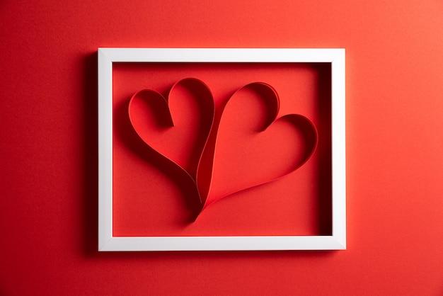 Zwei rote papierherzen im weißen bilderrahmen