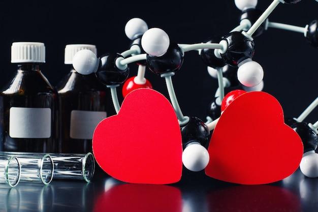 Zwei rote papierherzen und molekülstruktur modellieren auf einem schwarzen. liebe chemiekonzept