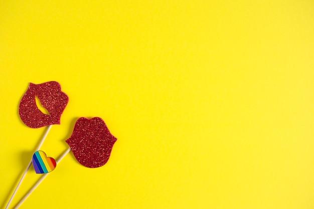 Zwei rote papierküsse auf stöcken und regenbogenherzabzeichen auf gelbem hintergrund. lesbenliebe. lgbt-konzept
