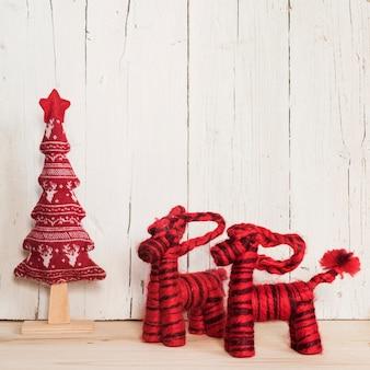Zwei rote rentiere und baum für weihnachten