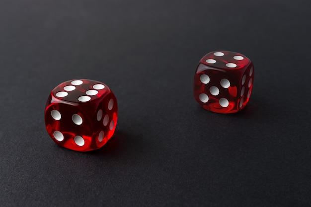 Zwei rote spielwürfel auf schwarzem tisch