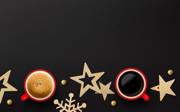 Zwei rote tasse kaffee- und weihnachtsdekoration auf schwarzem papierhintergrund