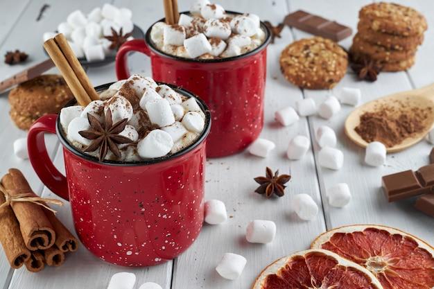 Zwei rote tassen heiße schokolade mit marshmallow, anis und zimt, bestreut mit kakaopulver