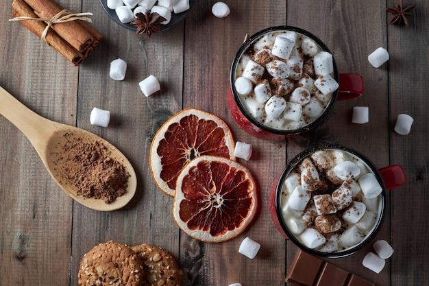Zwei rote tassen heiße schokolade mit marshmallow, bestreut mit kakaopulver, auf einem holztisch mit scheiben getrockneter grapefruit und schokoladenstücken. heißes wintergetränk mit gewürzen. draufsicht.