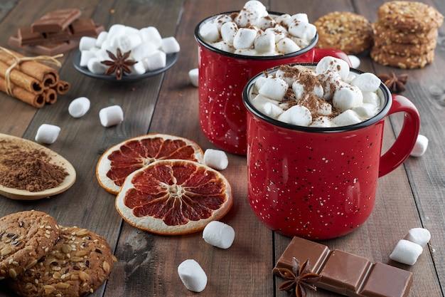 Zwei rote tassen heiße schokolade mit marshmallow, bestreut mit kakaopulver, auf einem holztisch mit scheiben getrockneter grapefruit und schokoladenstücken. heißes wintergetränk mit gewürzen.