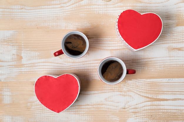 Zwei rote tassen kaffee und herzförmige kisten. datum, valentinstag. ansicht von oben