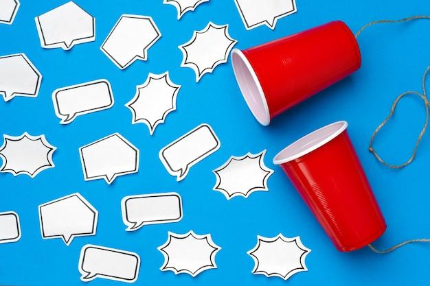 Zwei rote tassen, verbunden mit einem faden mit sprechblasen auf blauer oberfläche